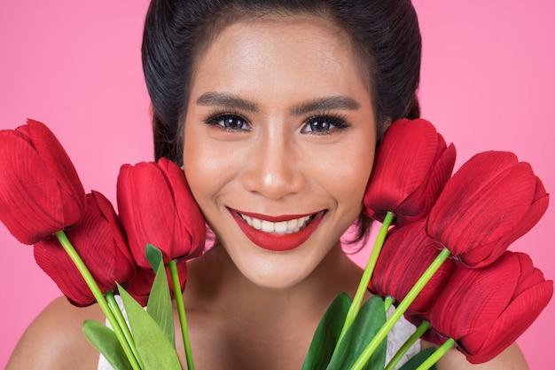 Portret piękna kobieta z bukietem czerwoni tulipanowi kwiaty