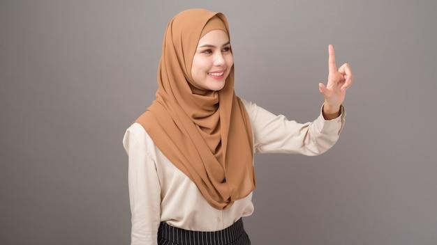 Portret piękna kobieta z hidżabem dotyka wirtualnego ekranu na szarości ścianie