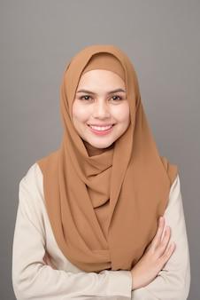 Portret piękna kobieta z hijab jest uśmiechnięta na szarym tle