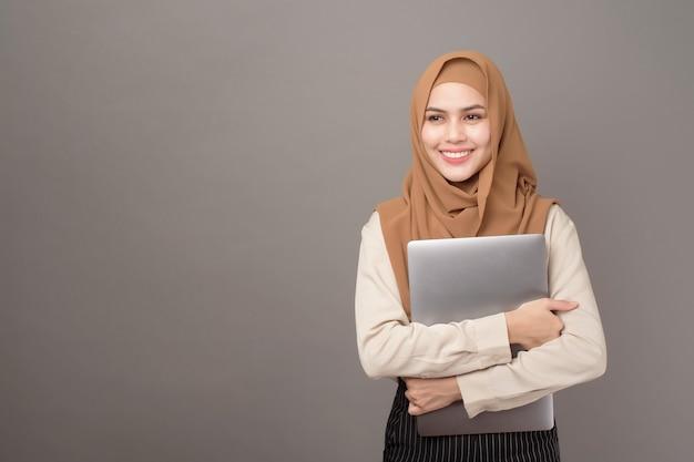 Portret piękna kobieta z hijab trzyma komputerowego laptop