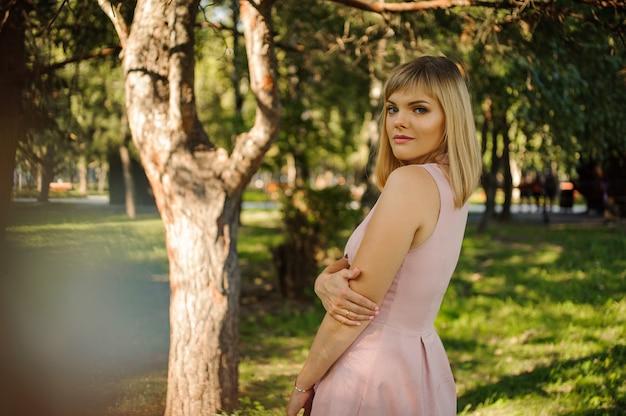 Portret piękna kobiety pozycja blisko drzewa w zielonym parku w lecie