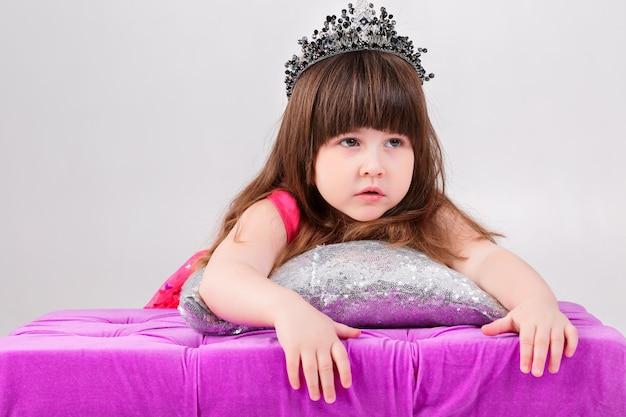 Portret piękna mała brunetka dziewczynka w różowej sukience księżniczki z koroną na srebrnej poduszce na szarym tle. słodkie dziecko