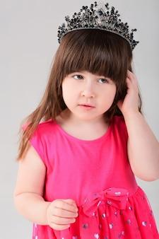 Portret piękna mała brunetka dziewczynka w różowej sukience księżniczki z koroną na szarym tle. słodkie dziecko