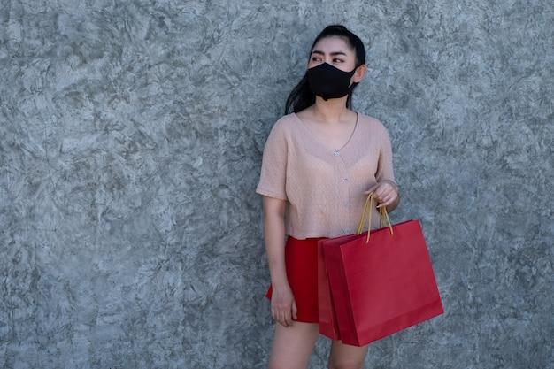 Portret piękna młoda azja kobieta jest ubranym maskę z mień torba na zakupy przy betonową ścianą