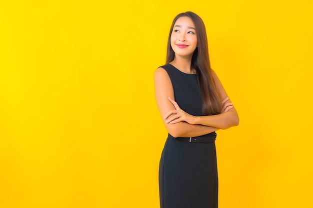 Portret piękna młoda azjatycka biznes kobieta uśmiech z akcją na żółtym tle koloru