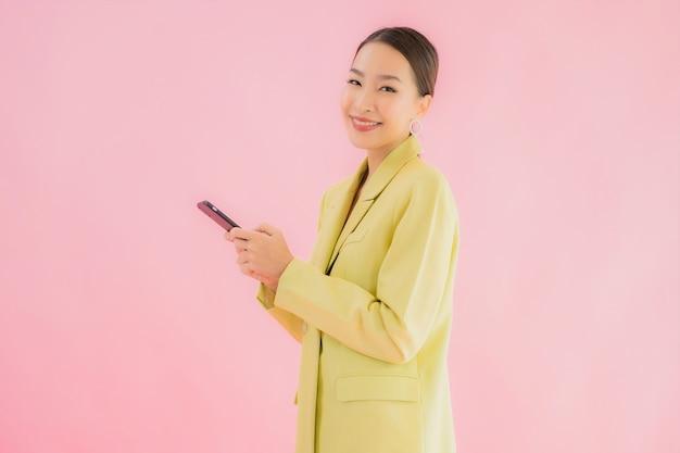 Portret piękna młoda azjatycka biznesowa kobieta używa inteligentnego telefonu komórkowego z filiżanką kawy na kolor