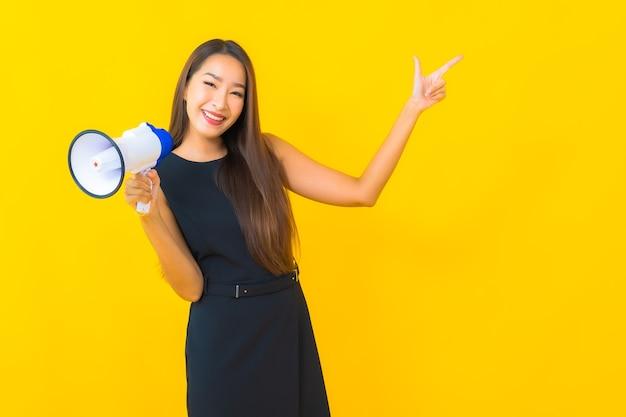 Portret piękna młoda azjatycka biznesowa kobieta używa megafonu do komunikacji