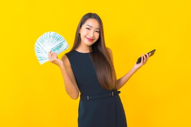 Portret piękna młoda azjatycka biznesowa kobieta z dużą ilością gotówki i pieniędzy na żółtym tle