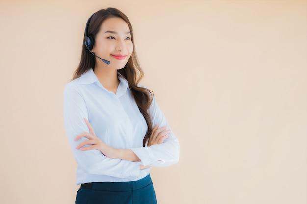 Portret piękna młoda azjatycka biznesowa kobieta z hełmofonem dla call center