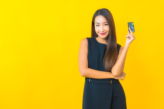 Portret piękna młoda azjatycka biznesowa kobieta z kartą kredytową na żółtym tle