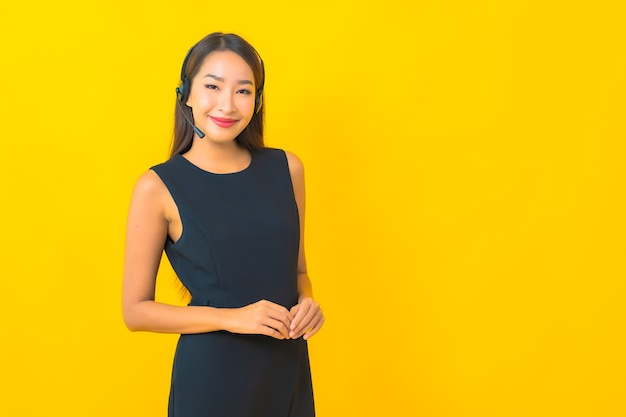 Portret piękna młoda azjatycka biznesowa kobieta z obsługą klienta call center zestawu słuchawkowego na żółtym tle