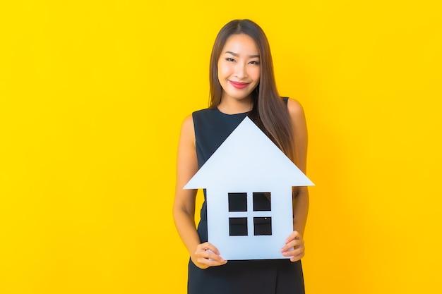 Portret piękna młoda azjatycka biznesowa kobieta z tablicą znak domu na żółtym tle