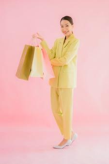 Portret piękna młoda azjatycka biznesowa kobieta z torbą na zakupy na kolor na białym tle