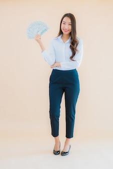 Portret piękna młoda azjatycka kobieta biznesu gotówką lub pieniądze