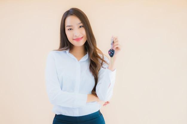 Portret piękna młoda azjatycka kobieta biznesu z kluczykiem samochodowym