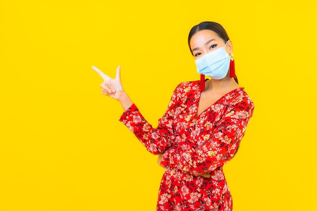 Portret piękna młoda azjatycka kobieta nosi maskę do ochrony wirusa koronowego lub covid19 na żółtej ścianie