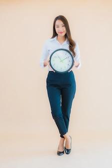 Portret piękna młoda azjatycka kobieta pokazuje budzik lub zegar