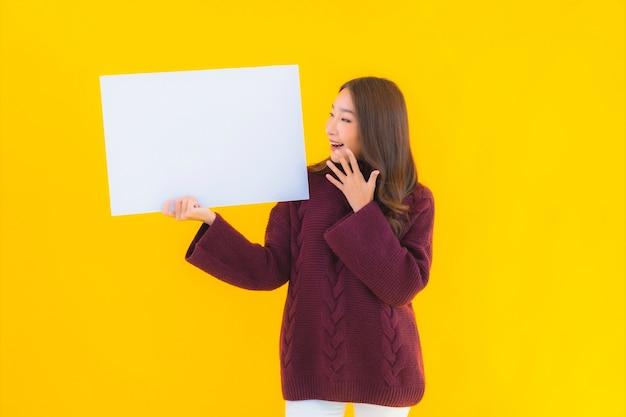 Portret piękna młoda azjatycka kobieta pokazuje pustą białą tekturę