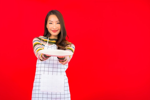 Portret piękna młoda azjatycka kobieta pokazuje puste naczynie na czerwonej ścianie