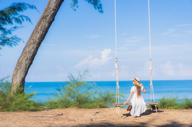 Portret piękna młoda azjatycka kobieta relaksuje uśmiech na huśtawce wokół plaży oceanu morskiego na podróż natury w wakacje