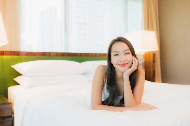 Portret piękna młoda azjatycka kobieta relaksuje uśmiech na łóżku we wnętrzu sypialni