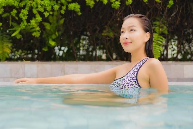 Portret piękna młoda azjatycka kobieta relaksuje uśmiech wokół odkrytego basenu na wypoczynek i wakacje