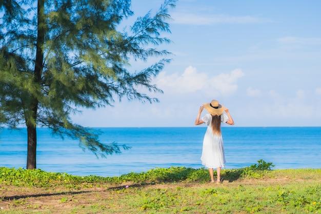 Portret piękna młoda azjatycka kobieta relaksuje uśmiech wokół plaży oceanu morskiego z błękitnym niebem białą chmurą na wakacje w podróży