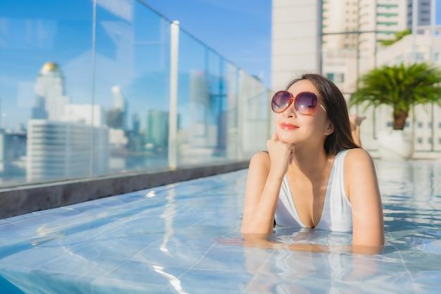 Portret piękna młoda azjatycka kobieta relaksuje wypoczynek przy basenie