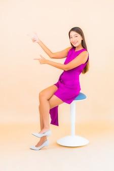 Portret piękna młoda azjatycka kobieta siedzi na krześle z kolorowym tłem
