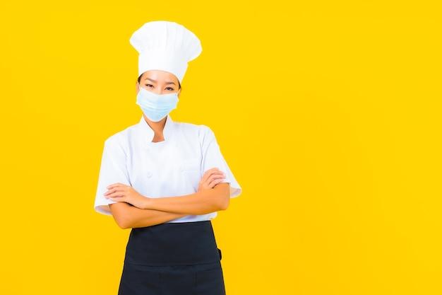 Portret piękna młoda azjatycka kobieta szefa kuchni nosi maskę do ochrony covid19 lub koronawirusa na żółtym tle na białym tle