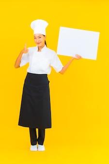 Portret piękna młoda azjatycka kobieta szefa kuchni z białym pustym billboardem na żółtym tle na białym tle