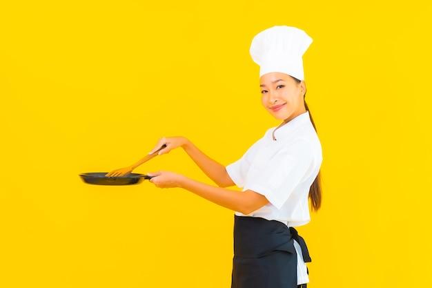Portret piękna młoda azjatycka kobieta szefa kuchni z czarną patelnią na żółtym tle na białym tle