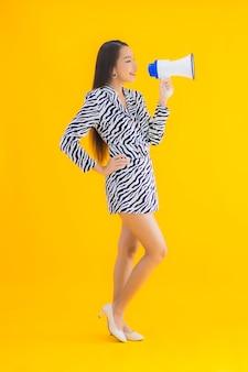 Portret piękna młoda azjatycka kobieta uśmiech szczęśliwy z megafonem na żółto