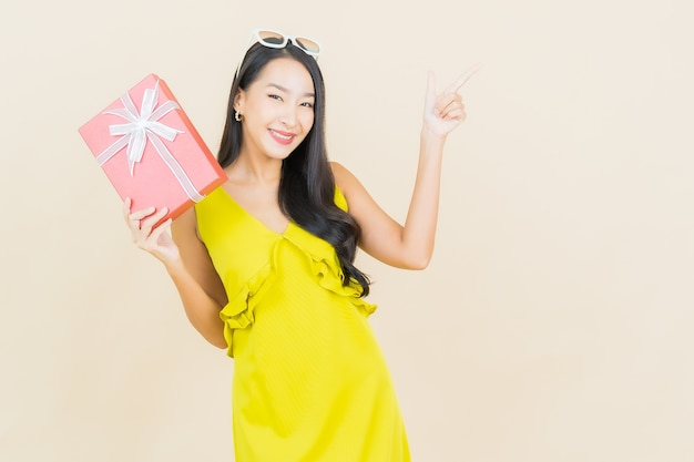 Portret piękna młoda azjatycka kobieta uśmiech z czerwonym pudełkiem na ścianie koloru