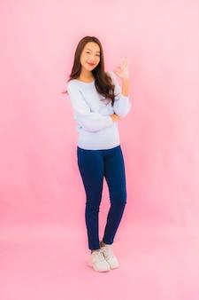 Portret piękna młoda azjatycka kobieta uśmiech z działaniem na różowej ścianie na białym tle