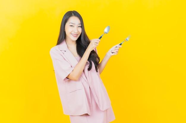 Portret piękna młoda azjatycka kobieta uśmiecha się łyżką i widelcem na żółtej ścianie