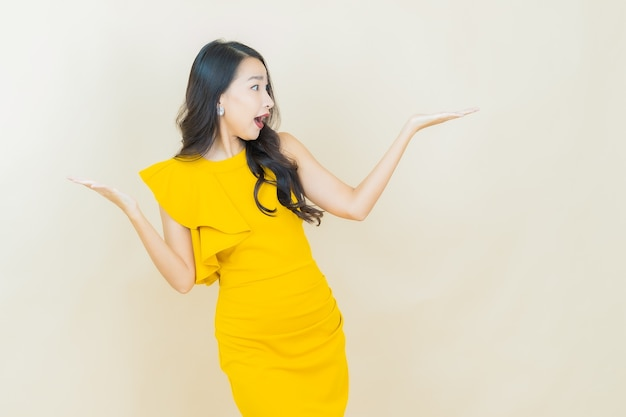Portret piękna młoda azjatycka kobieta uśmiecha się na beżowej ścianie