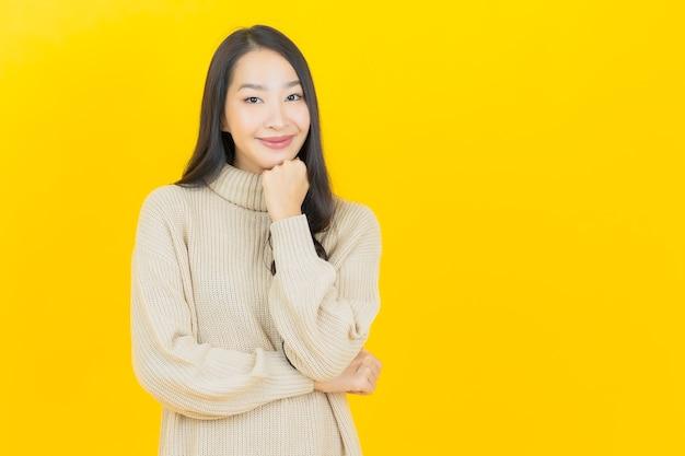 Portret piękna młoda azjatycka kobieta uśmiecha się z akcją na żółtej ścianie