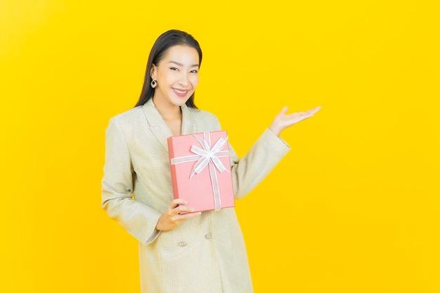 Portret piękna młoda azjatycka kobieta uśmiecha się z czerwonym pudełkiem na kolorowej ścianie