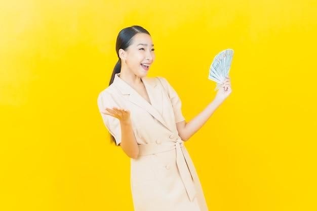 Portret piękna młoda azjatycka kobieta uśmiecha się z dużą ilością gotówki i pieniędzy na kolorowej ścianie