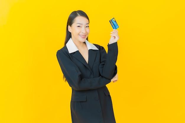 Portret piękna młoda azjatycka kobieta uśmiecha się z kartą kredytową na kolorowej ścianie