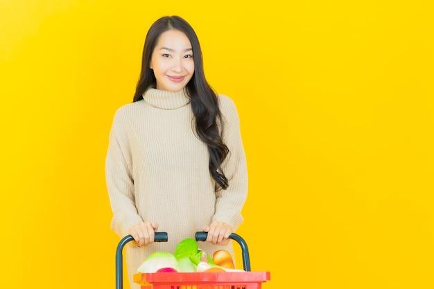 Portret piękna młoda azjatycka kobieta uśmiecha się z koszem spożywczym z supermarketu na żółtej ścianie