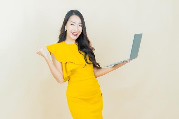 Portret piękna młoda azjatycka kobieta uśmiecha się z laptopem komputerowym na na białym tle
