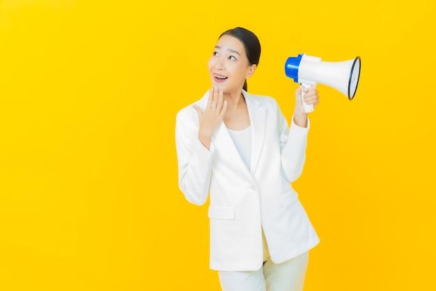 Portret piękna młoda azjatycka kobieta uśmiecha się z megafonem na kolorowej ścianie