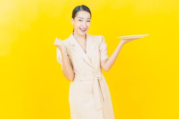 Portret piękna młoda azjatycka kobieta uśmiecha się z pustym talerzem na kolorowej ścianie