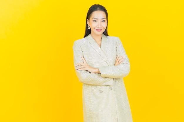 Portret piękna młoda azjatycka kobieta uśmiecha się ze skrzyżowanymi rękami na kolorowej ścianie