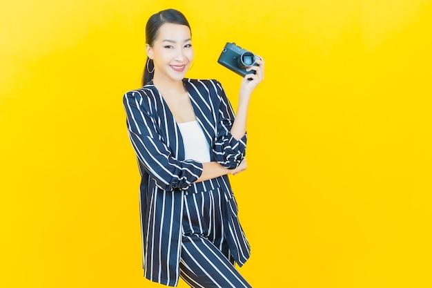 Portret piękna młoda azjatycka kobieta używa aparatu na kolorowym tle