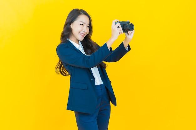 Portret piękna młoda azjatycka kobieta używa aparatu na żółto