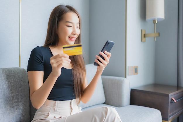 Portret piękna młoda azjatycka kobieta używa inteligentnego telefonu komórkowego lub laptopa z kartą kredytową na kanapie w salonie