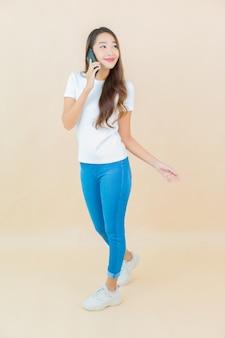 Portret piękna młoda azjatycka kobieta używa inteligentnego telefonu komórkowego na beżu